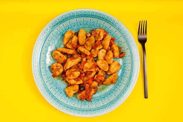 Piatto celeste di gnocchi al sugo rosso su tavola gialla. accompagna una moderna forchetta nera. cibo italiano.