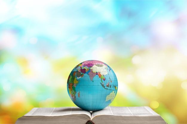 Libro pesante e globo sullo sfondo