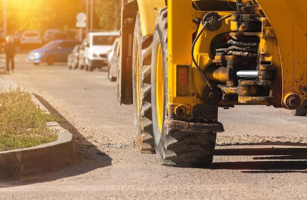 Macchinari pesanti, escavatore in cantiere, primo piano delle grandi ruote, banner