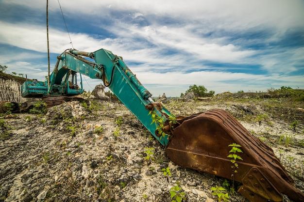 Escavatore pesante, vecchio e rotto con pala in piedi su una collina con rocce
