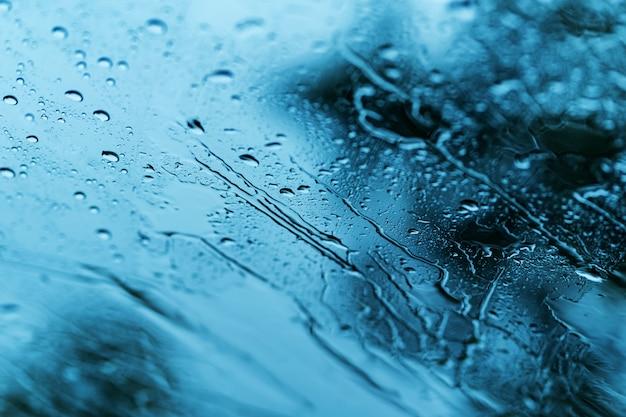 Fondo della pioggia persistente, gocce di pioggia sul vetro di finestra all'aperto
