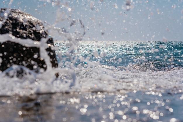 Un'onda del mare pesante si rompe in schizzi di schiuma bianca sulla riva