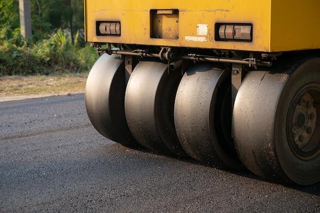 Rullo compressore giallo a vibrazione pesante o compattatore per terreno che lavora su asfalto a caldo