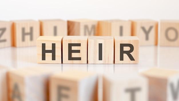 Parola di erede da blocchi di legno con lettere, erede o concetto di affari, lettere casuali intorno, sfondo bianco