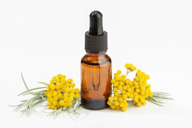 Olio essenziale di elicriso sulla bottiglia ambrata isolata su fondo bianco. olio alle erbe