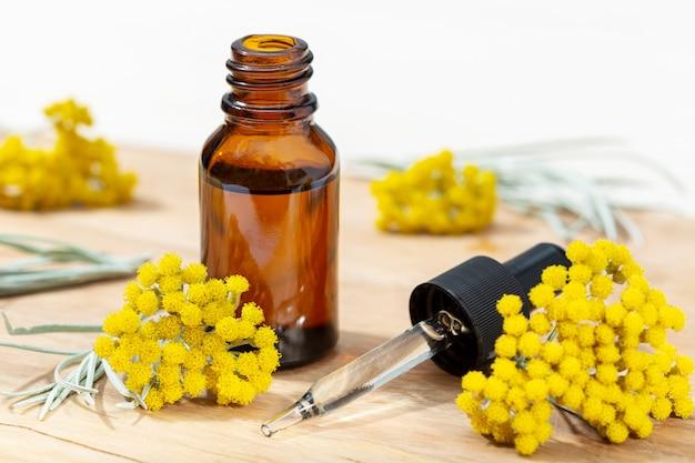 Olio essenziale di elicriso in bottiglia ambrata e pipetta. rimedi a base di erbe olio