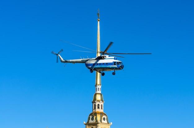 Elicottero nel cielo contro la guglia della fortezza di pietro e paolo a san pietroburgo.