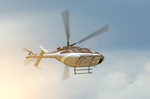 L'elicottero gira volando nel cielo in una giornata nuvolosa.