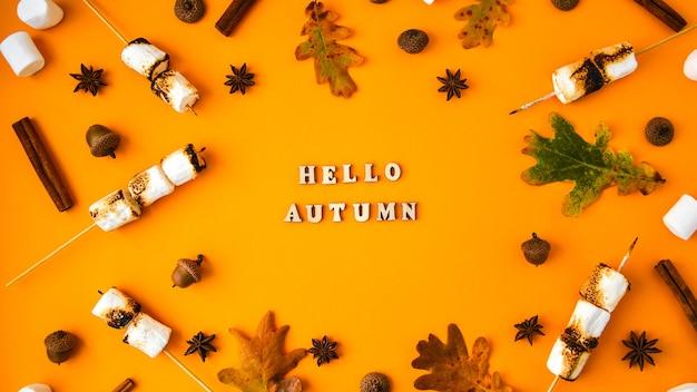 Ciao autunno testo. foglie di marshmallow alla cannella e anice su sfondo giallo. composizione autunnale. modello fatto di cose autunnali. disposizione piatta. ornamento per il ringraziamento. cornice autunnale con spazio di copia.