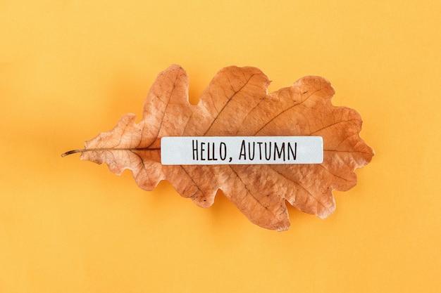 Ciao testo autunnale e foglia di quercia su sfondo giallo. vista dall'alto piatto stile minimal. concetto benvenuto autunno. biglietto d'auguri.