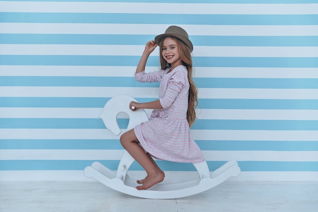 Ciao! bambina carina che si aggiusta il cappello e guarda la telecamera con un sorriso