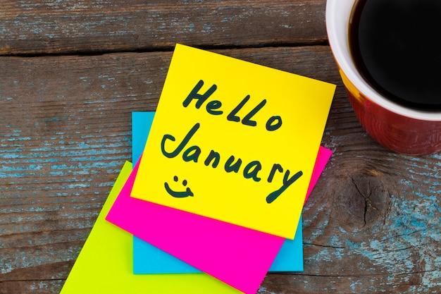 Ciao gennaio - scrittura a mano con inchiostro nero su una nota adesiva con una tazza di caffè, concetto di risoluzioni per il nuovo anno.