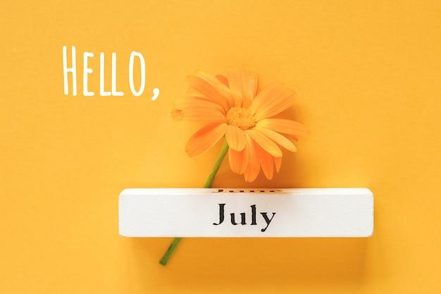 Ciao testo di luglio, biglietto di auguri. un fiore di calendula arancione e un mese estivo del calendario luglio su sfondo giallo. vista dall'alto copia spazio piatto stile minimal.