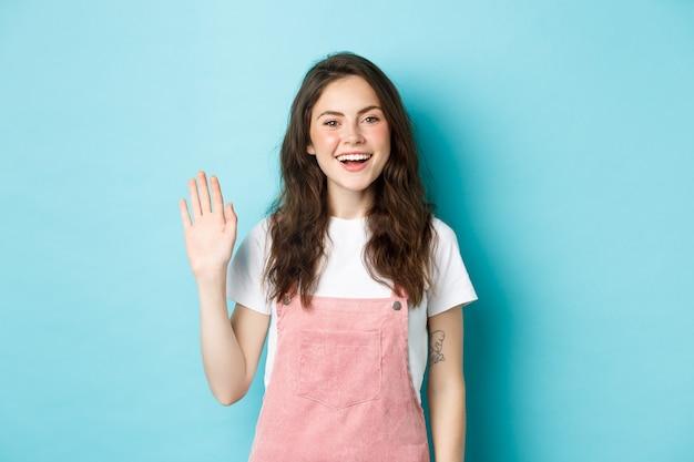 Ciao, piacere di conoscerti. bella ragazza amichevole che agita la mano per salutare, sembra felice e sorridente mentre ti saluta, ti dà un caloroso benvenuto, in piedi su sfondo blu