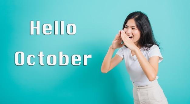 Ciao october portrait bella giovane donna asiatica felice che grida con le mani che coprono la bocca