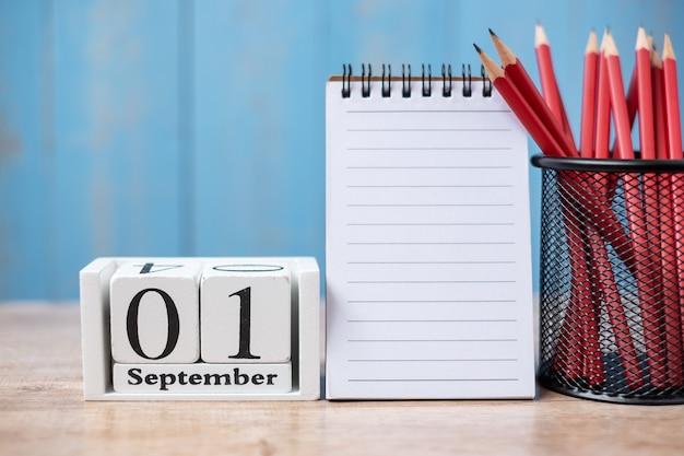 Ciao calendario di settembre, bentornati a scuola con quaderno e matite. copia spazio per il testo