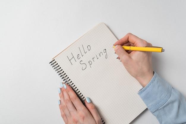 Ciao avviso di motivazione di primavera. le mani femminili scrivono nel blocco note su sfondo bianco.
