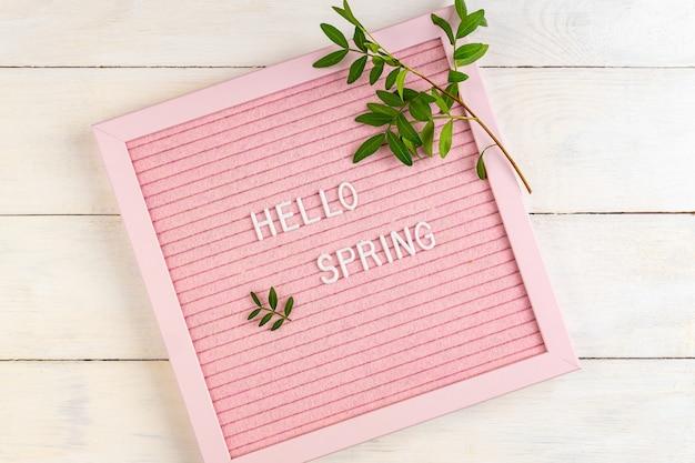 Ciao primavera sulla lavagna da lettere rosa con rami verdi su fondo in legno