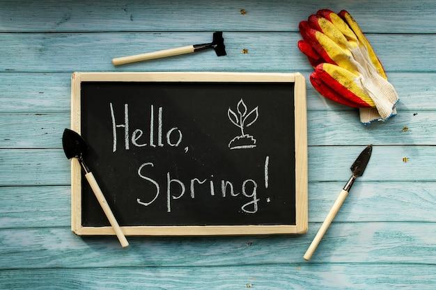 Ciao primavera. sfondo di composizione di primavera, carta da parati. attrezzatura per piantare, preparazione. strumenti e guanti. foto di alta qualità