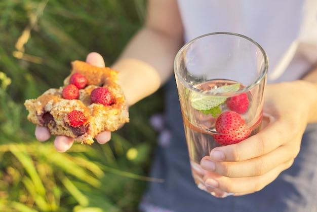 Ciao stagione delle fragole, primo piano della torta torta fatta in casa con fragole e vetro con bevanda alla menta fragola