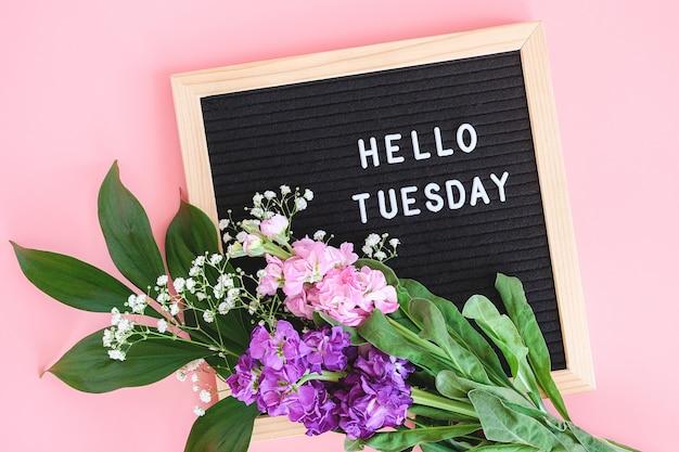 Ciao martedì testo sulla bacheca nera e bouquet di fiori colorati su sfondo rosa.