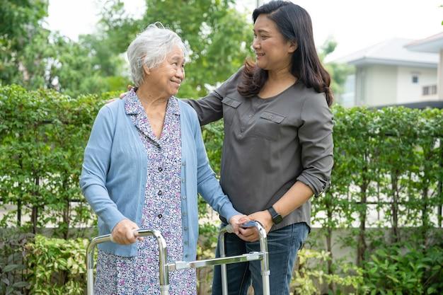 Aiuto e cura la donna anziana o anziana asiatica usa il camminatore con una buona salute mentre cammina al parco in una felice vacanza fresca.