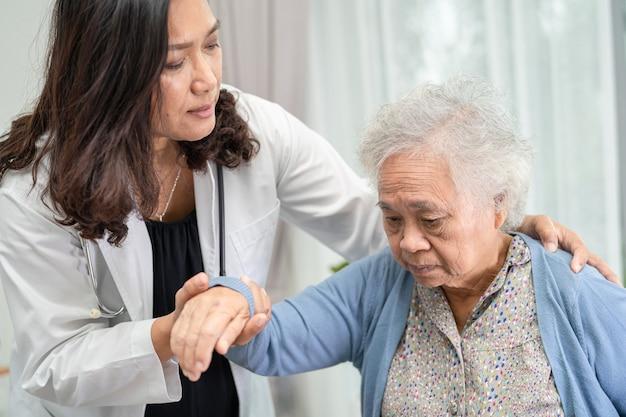 Aiutare e prendersi cura di una paziente asiatica anziana seduta su una sedia a rotelle in ospedale