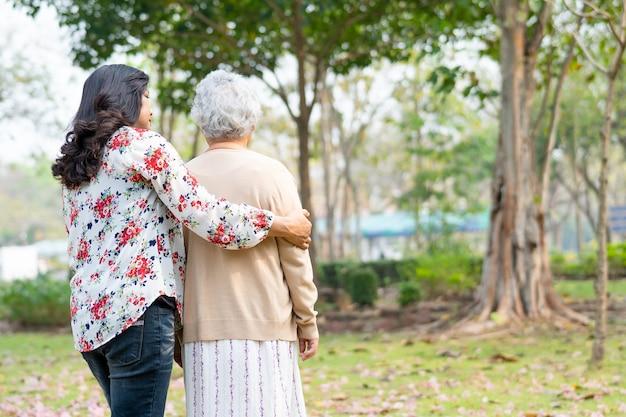 Aiutare e prendersi cura della donna asiatica senior che cammina al parco.