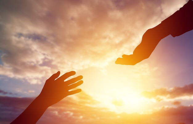 Aiuta la mano sullo sfondo del tramonto