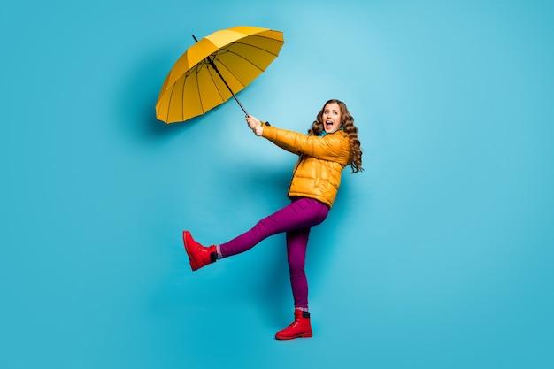 Aiutami! foto di profilo a grandezza naturale della signora scioccata pazza tenere l'ombrello volare con il vento che soffia indossare sciarpa cappotto giallo pantaloni viola scarpe rosse isolato muro di colore blu