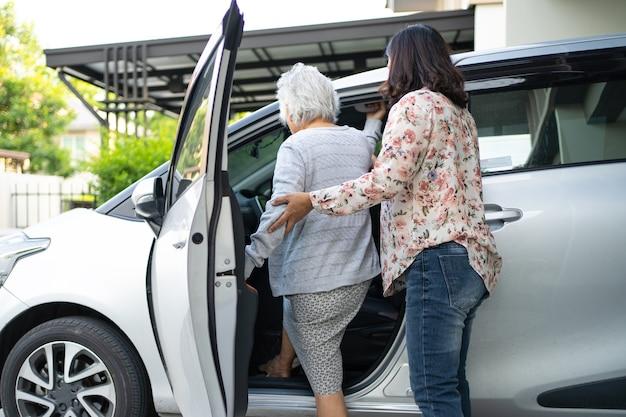 Aiutare e supportare la paziente asiatica anziana o anziana anziana prepararsi per raggiungere la sua auto.