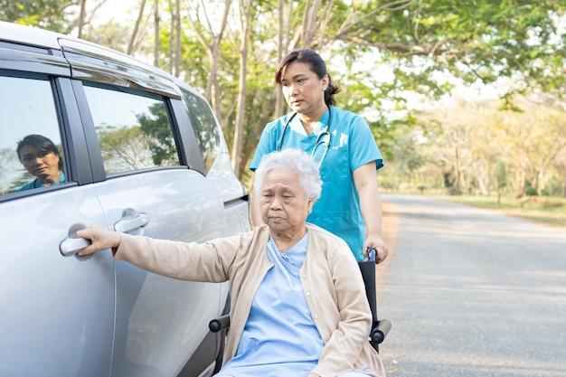 Aiutare e sostenere una paziente asiatica anziana o anziana anziana seduta su sedia a rotelle prepararsi a raggiungere la sua auto: concetto medico sano
