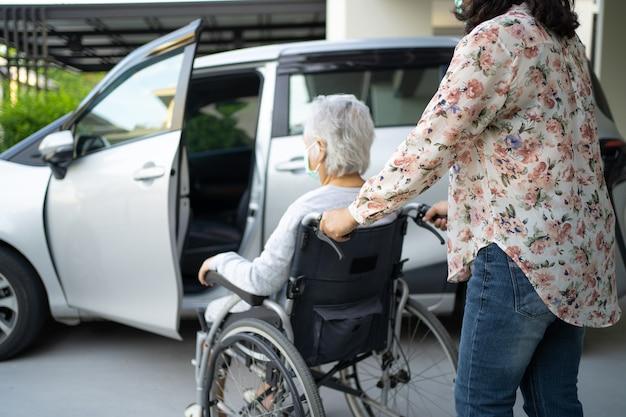 Aiutare e supportare una paziente asiatica anziana seduta su una sedia a rotelle prepararsi a raggiungere la sua auto