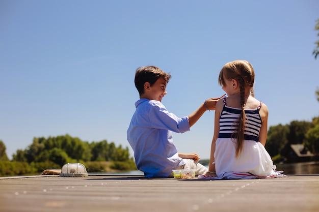 Aiuta te stesso. piacevole ragazzo preadolescenziale che alimenta la sua sorellina mentre è seduto sul molo insieme a lei