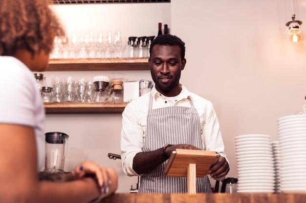 Consigli utili. uomo simpatico positivo che parla con un cliente mentre le consiglia cosa ordinare
