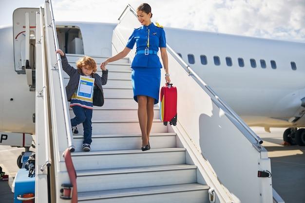 Utile hostess della compagnia aerea che aiuta un bambino a uscire da un aereo