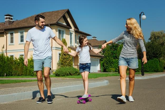 Supporto utile. giovani genitori allegri che insegnano alla loro amata figlia a cavalcare uno skateboard, tenendole le mani sostenendola