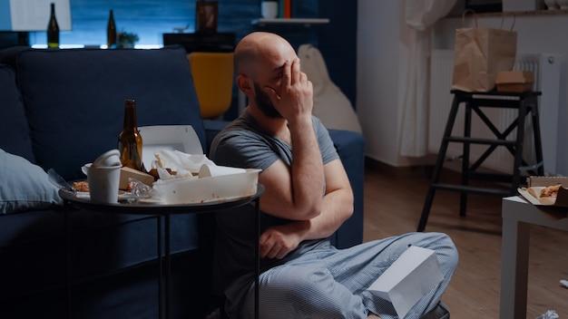 Indifeso, frustrato, confuso, adulto, disperato, uomo adulto seduto sul pavimento che legge con un avviso di sfratto delle lacrime