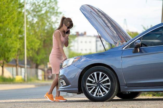 Donna impotente in piedi vicino alla sua auto con il cofano aperto che chiama il servizio stradale per chiedere aiuto. giovane conducente femminile che ha problemi con il veicolo.