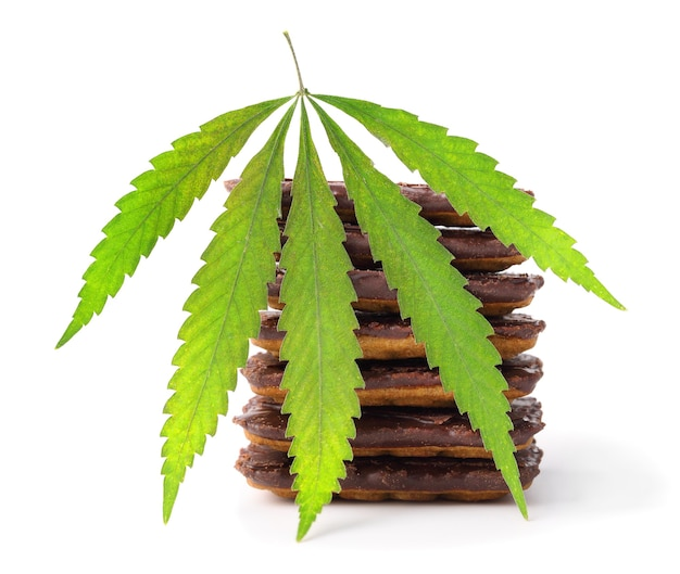 Foglia di canapa accanto a biscotti con gocce di cioccolato con contenuto di cannabis cbd
