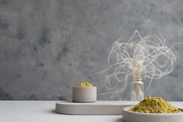 Polvere di henné per tingere capelli e sopracciglia e disegnare mehendi sulle mani su un piedistallo di cemento grigio con fiori secchi o un fiore bianco.