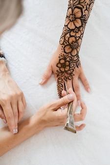 Tatuaggio all'henné su mani di donna artista disegno arabo mehndi