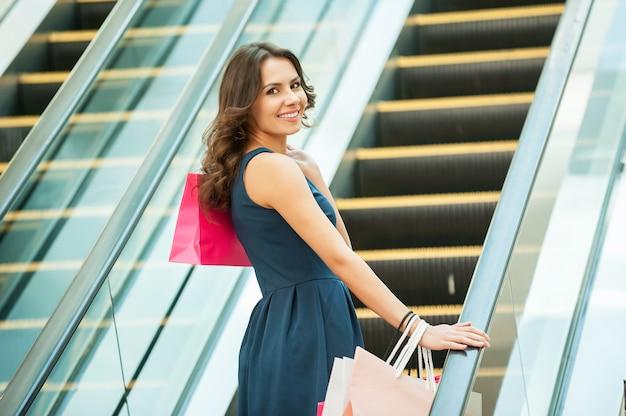 Sulla strada per il prossimo negozio. vista posteriore della bella giovane donna con le borse della spesa sulla scala mobile del centro commerciale