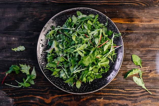 Insalata verde alle erbe con rucola, spinaci e bietole. insalata di salute vegetariana. vista dall'alto