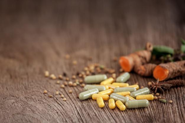 Capsule a base di erbe con pianta medicinale sana su sfondo di legno