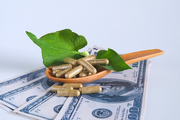 Capsule a base di erbe su foglia di erba verde sulla banconota del dollaro.