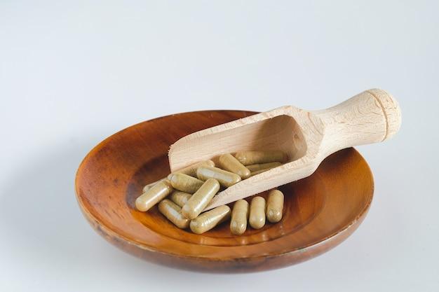Capsule di erbe su cucchiaio di legno con foglia di erbe su bianco