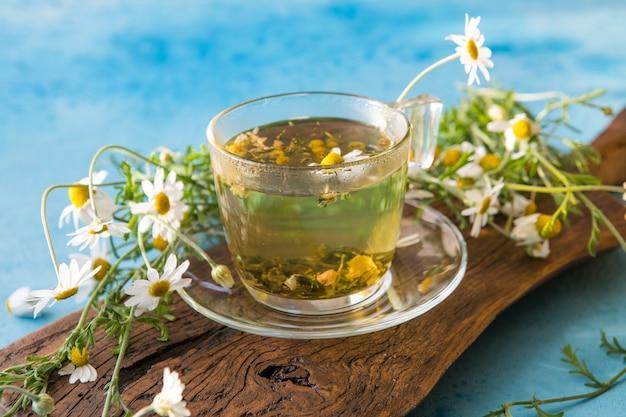 Camomilla alle erbe e fiori di camomilla su tavola di legno su sfondo blu