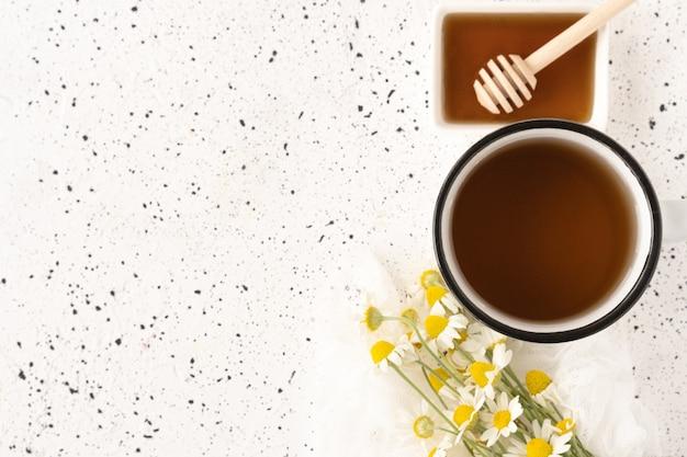 Camomilla alle erbe in tazza bianca e miele su fondo di cemento bianco.