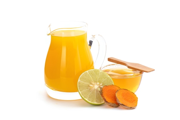 Bevanda a base di erbe con curcuma, limone e miele isolato su sfondo bianco.